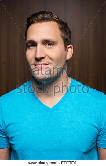 Portrait of smiling man in blue t-shirt - Stock Image