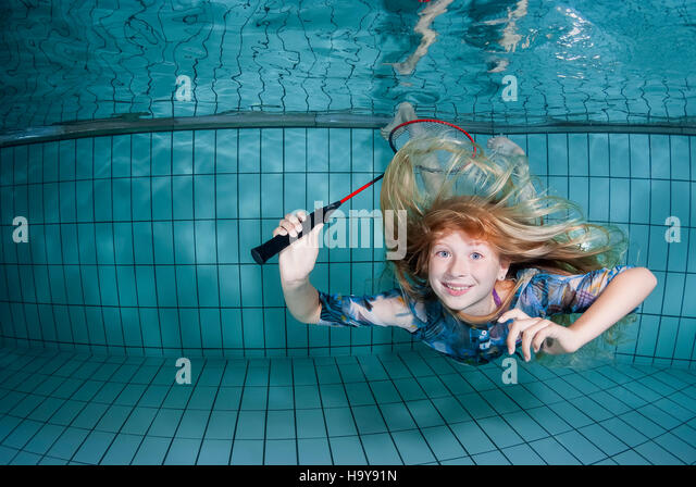 Pretty young girl underwater playing badminton under water in a swimming pool - Stock Image