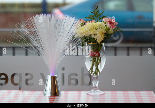 Mare's tail and flower arrangement in a beer glass and a Felixstowe cafe - Stock Image