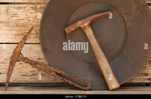 Mining picks with gold pan on old weathered shelf. - Stock Image