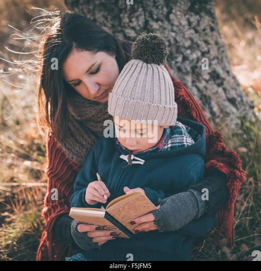 Mother helping her son writing first letters - Stock Image