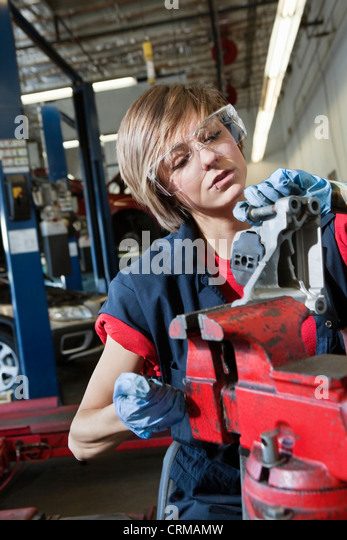 Young female mechanic in protective workwear working on machinery part in automobile repair shop - Stock Image
