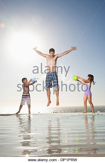 Children splashing water on man - Stock Image