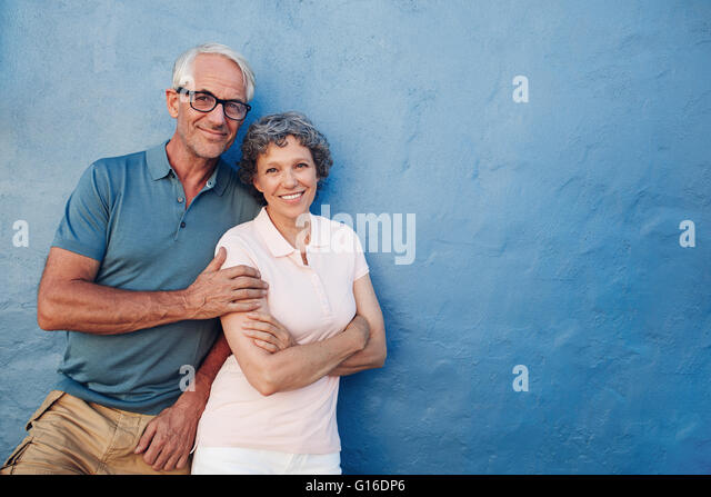 Portrait of happy senior man and woman together against blue background. Middle aged couple looking at camera and - Stock Image