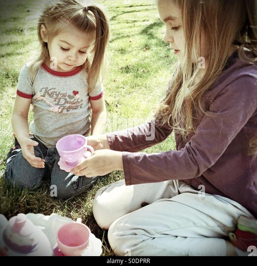 Two young sisters enjoying a tea party on the lawn - Stock Image