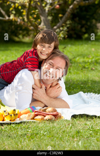 Germany, Bavaria, Father and son (10-11) having fun at picnic - Stock Image