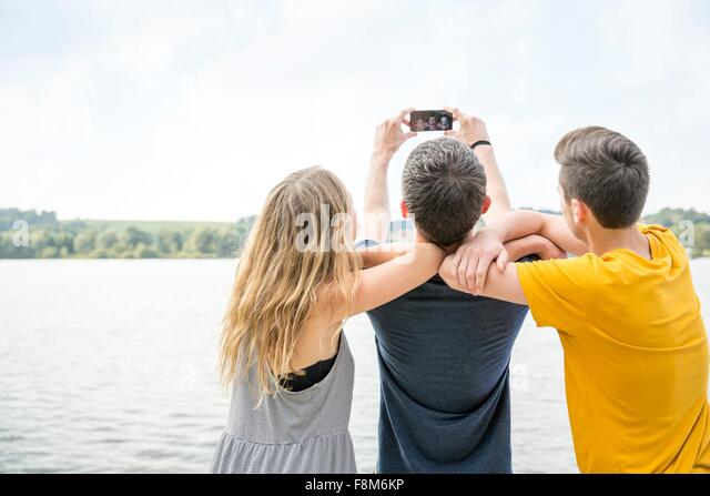 Three young adults taking self portrait using smartphone, rear view - Stock Image