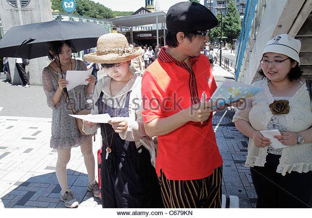 Japan Tokyo Harajuku JR Harajuku Station Asian man woman women reading survey questionnaire group - Stock Image