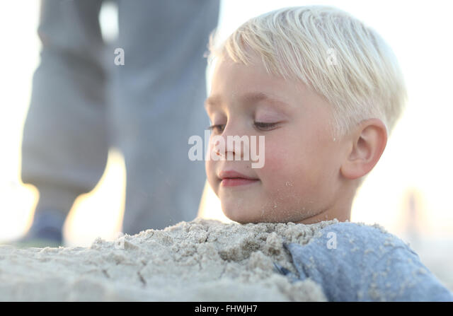 Fun in the sand on the beach . Child on beach . Cheerful little boy playing in the sand on the beach. Fun on the - Stock Image