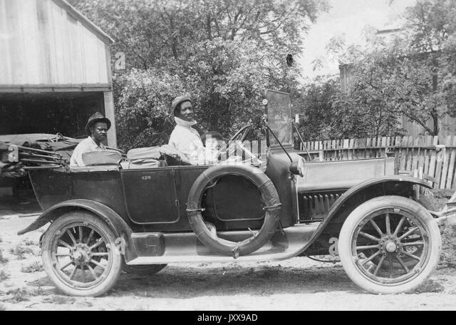 Full length landscape shot of two African American mature men in a car, one man in the back, one man at the steering - Stock Image