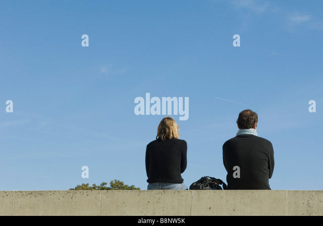 Couple sitting on ledge, rear view - Stock Image