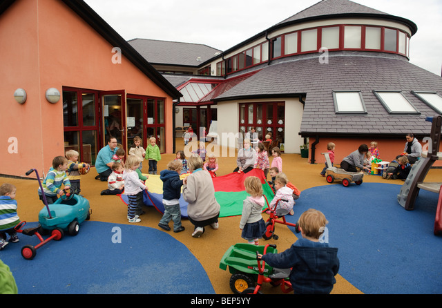 small children playing outdoors at a Pre school nursery creche or kindergarten Wales UK - Stock Image