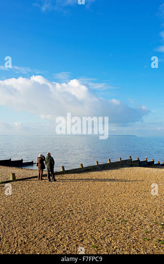 Middle-aged couple on the beach at Whitstable, Kent, England UK - Stock Image