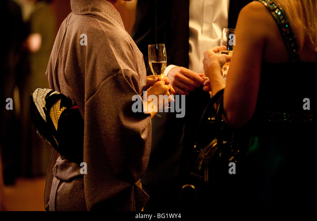 Japanese woman in kimono drinking champagne with Woman in Western style dress, and man in black tie.. - Stock-Bilder