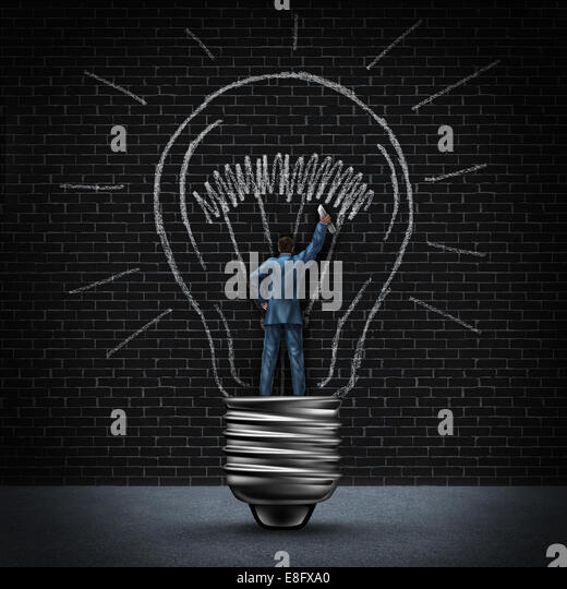 Light bulb man business concept as a businessman standing in a light base and drawing an illuminated glowing bulb - Stock Image