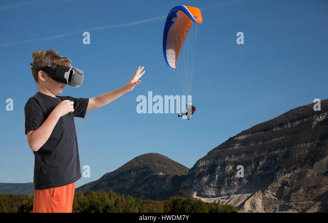 Young boy wearing virtual reality headset, reaching out to touch paraglider, digital composite - Stock-Bilder