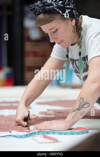 Young tattooed seamstress cutting out a pattern - Stock-Bilder