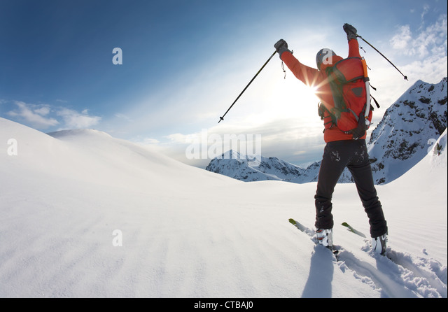 Young skier reaches his arms up over a snowy mountain landscape, italian alps; horizontal frame - Stock Image