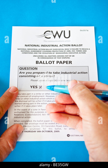 A Royal Mail postman employee ticking the yes box for strike action on the official national ballot paper for 8th - Stock Image