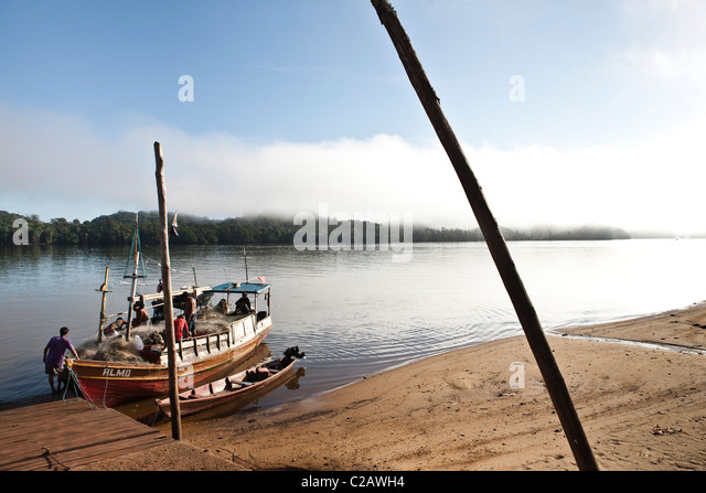 South America, Amazon, fishermen getting fishing boat into river - Stock Image