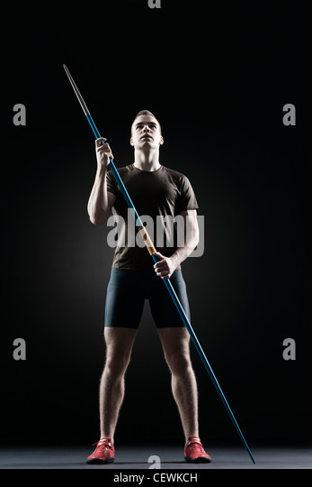 Male athlete standing with javeline - Stock Image