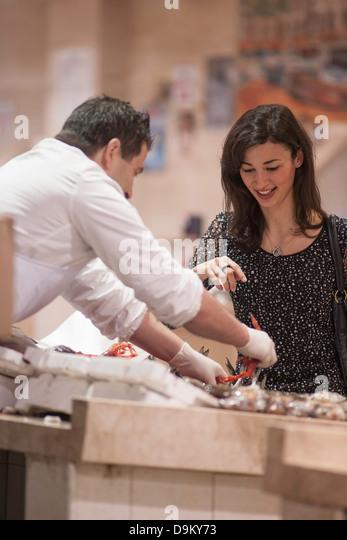 Woman buying fresh fish in market - Stock Image