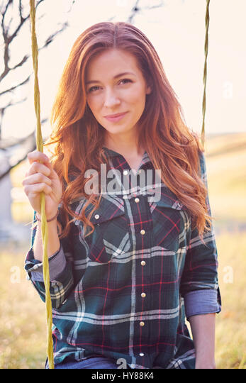 A carefree young women in jeans on a swing in a winter garden - Stock Image