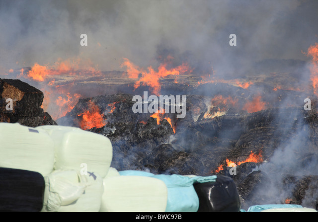 Fire destroys hay and farm equipment - Stock Image
