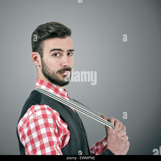 Desaturated portrait of young bearded hipster pulling his suspenders looking at camera over dark grey studio background - Stock-Bilder
