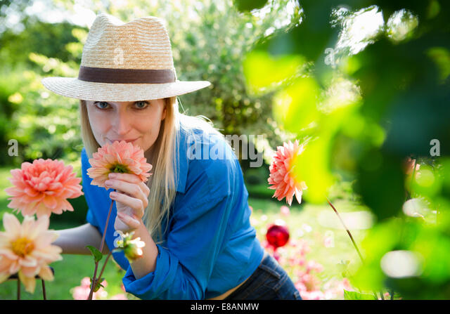 Portrait of mid adult woman smelling garden blooms - Stock Image