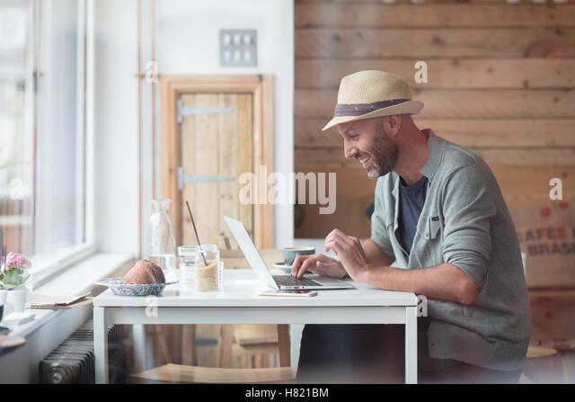 Mid 30s man working at laptop in cafe - Stock-Bilder