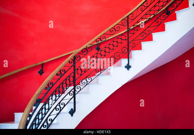 White sweeping staircase set against red wall, Habana, Havana, Cuba - Stock Image