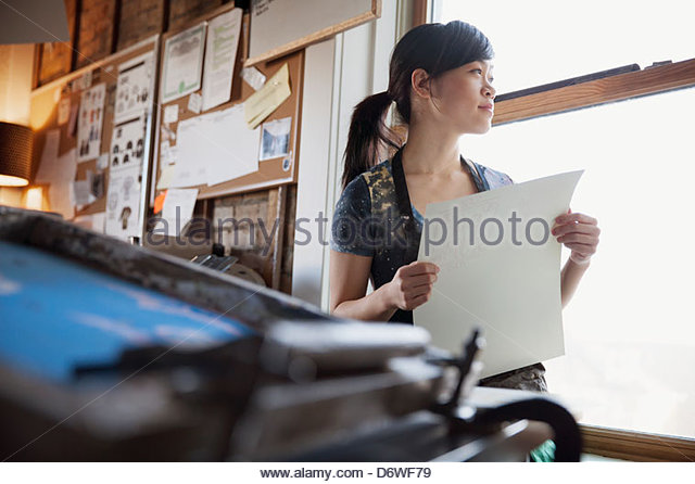 Thoughtful female design professional with print looking through window - Stock Image
