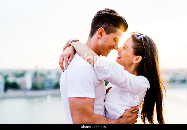 Young romantic couple hugging and about to kiss in beautiful sunset - Stock Image