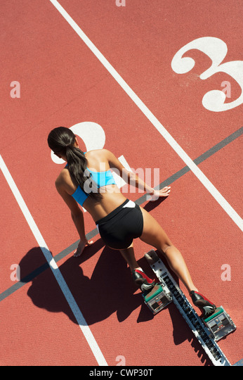 Female athlete in starting position on running track, rear view - Stock Image