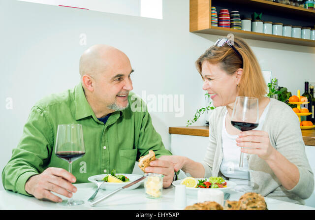 Senior couple having meal with red wine - Stock Image