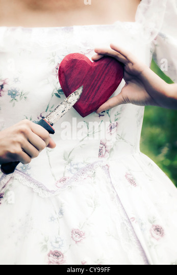 a woman in a period dress is holding a heart and a knife - Stock-Bilder