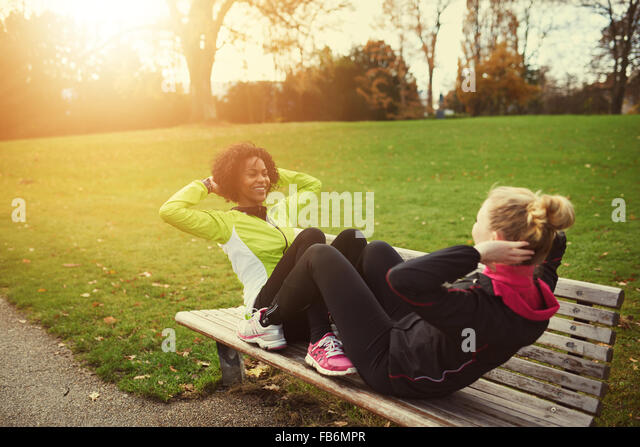 Two female athletes doing sit-ups on bench in park - Stock Image