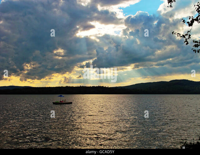 Sun rays coming through the clouds at a lake in northern Maine. - Stock Image
