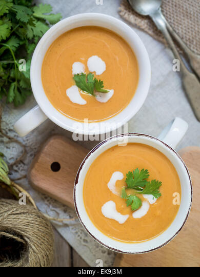 Two white cups with vegan (vegetarian) pumpkin cream soup with coconut milk, served with parsley, seen from above. - Stock Image