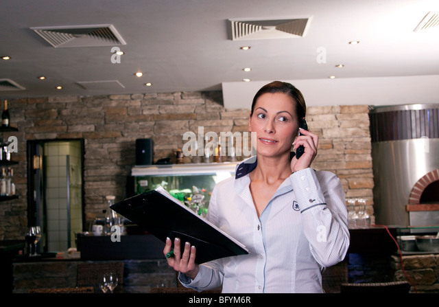 restaurant owner taking reservation on mobile phone - Stock Image