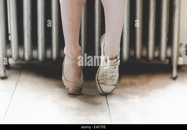 Dancer wearing one ballet shoe and one sneaker - Stock Image