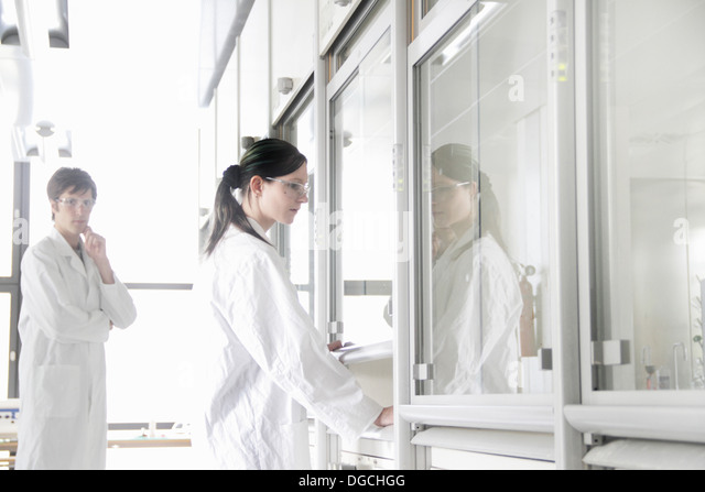 Chemistry students by fume cupboard in lab - Stock Image