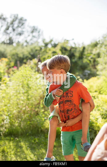 Sweden, Skane, Osterlen, Boy (10-11) giving piggyback ride to younger brother (8-9) - Stock Image
