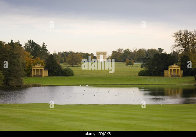 View across the Octagon Lake towards the Lake Pavilions and Corinthian Arch at Stowe Landscape Gardens, Buckinghamshire. - Stock-Bilder