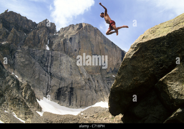 Man jumping off rock below Long's Peak, Rocky Mountain National Park, Estes Park, Colorado. - Stock Image
