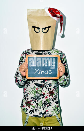 a young man dressing casual wear with a paper bag in his head and a santa hat in the top shows a chalkboard with - Stock Image