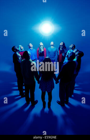 Group basking around bright light - Stock Image