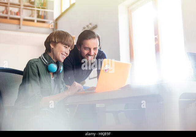 Smiling design professionals meeting at laptop in office - Stock-Bilder
