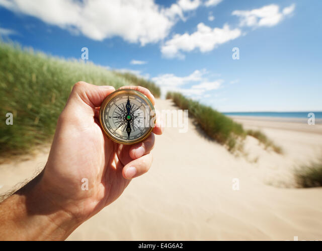 Hand holding a compass - Stock Image